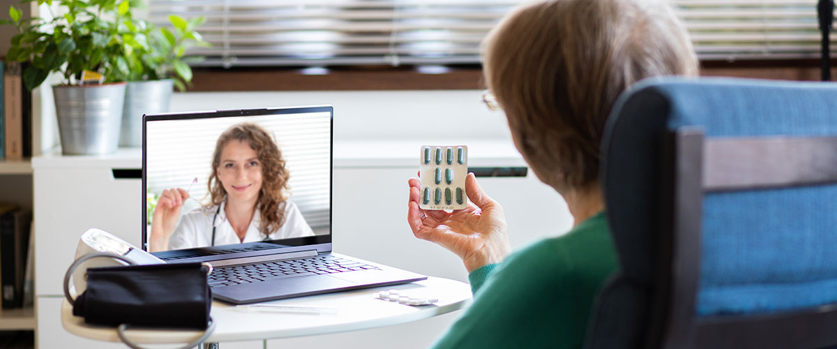 woman holding a blister pack of pillswhile talkingto a Telehealth doctor